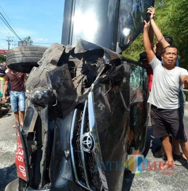 Polisi dan warga mengevakuasi mobil pelat merah yang terlibat kecelakaan di Jeblog, Talun.