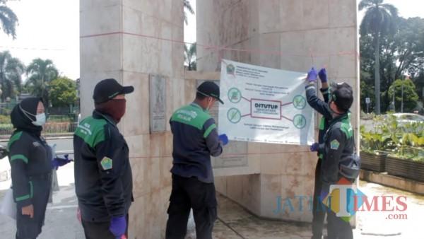 Pramu Taman saat melakukan pemasangan banner larangan masuk taman sementara (foto dok MalangTIMES)