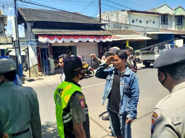 Salah satu warga yang terjaring operasi yustisi disanksi menyanyikan lagu Indonesia dengan melakukan penghormatan (Anggara Sudiongko/MalangTIMES)