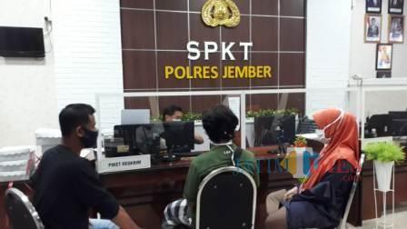 DSR (jilbab oranye) saat melaporkan kejadian yang dialaminya di Mapolres Jember. (foto : sid / Jatim TIMES)
