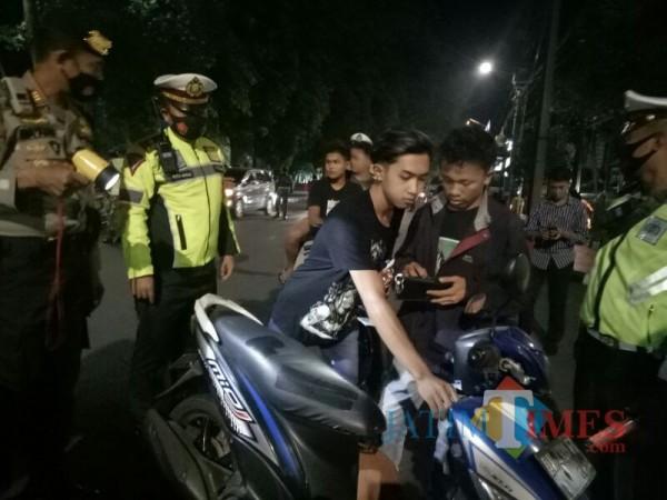 Dua remaja yang terjaring operasi Yustisi Masker, dan tidak menggunakan helm (Foto ; Moch. R. Abdul Fatah / Jatim TIMES)