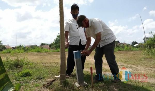 Petugas saat mengukur dan menasang pathok di lahan eks Kali Ngrowo (Joko Pramono for Jatim TIMES)