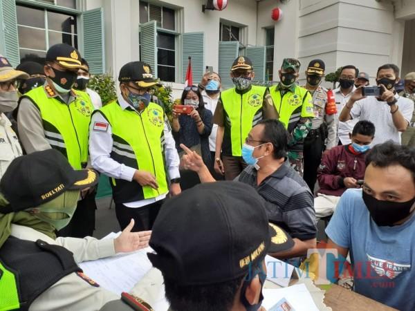 Bersitegang, seorang pelanggar adu mulut dengan Wali Kota Malang Sutiaji (bertopi). (Arifina Cahyanti Firdausi/MalangTIMES).
