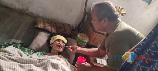 Kustomo saat menyuapi makanan ke istrinya yang lumpuh. (Foto : Adi Rosul / JombangTIMES)