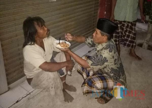 Kepala Desa Banjarejo, Kecamatan Rejotangan, Zaenuddin Jawahir saat menyuapi gelandangan. / Foto : Istimewa / Tulungagung TIMES