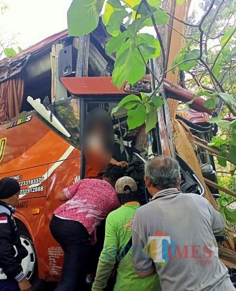 Warga memberikan pertolongan kepada sopir bus cepat Sugeng Rahayu yang menabrak pohon jati.