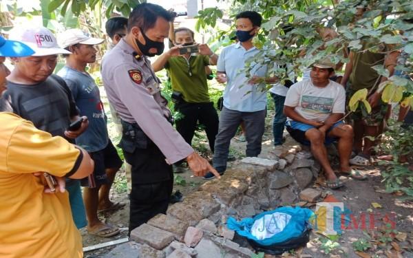Polisi menunjuk kain kafan yang ditemukan warga. (Foto : Adi Rosul / JombangTIMES)
