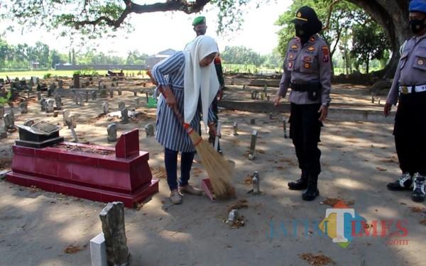 Warga bersihkan makam setelah terjaring razia Yustisi. (Foto: Adi Rosul/ JombangTIMES)