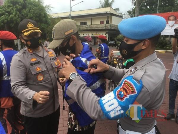 Kapolres Malang AKBP Hendri Umar (paling kiri) saat mengenakan rompi kepada relawan protokol kesehatan (Foto : Ashaq Lupito / MalangTIMES)
