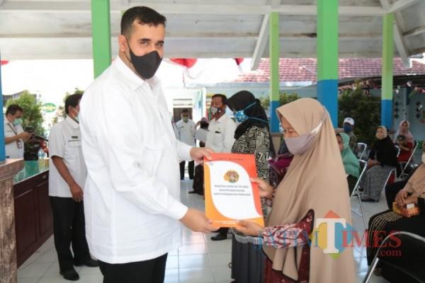 Wali Kota Probolinggo Habid Hadi (kiri) menyerahkan sertifikat kepada warga. (Foto: Mabrur/Probolinggotimes)
