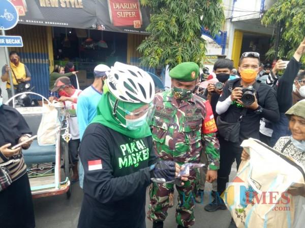 Gubernur Jatim Khofifah ketika menyerahkan sembako di Pasar Baru Lumajang (Foto : Moch. R. Abdul Fatah / Jatim TIMES)