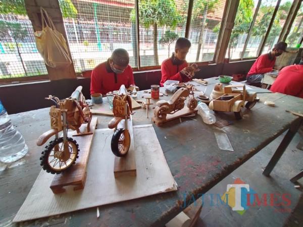 Nampak para napi tengah berada di bengkel seni membuat kerajinan miniatur motor, perahu dan mobil dari kayu (Anggara Sudiongko/MalangTIMES)