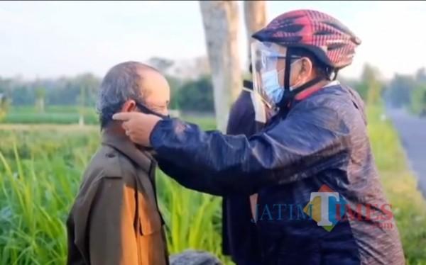 Rijanto membagi dan memakaikan masker kepada warga yang beraktivitas di sawah
