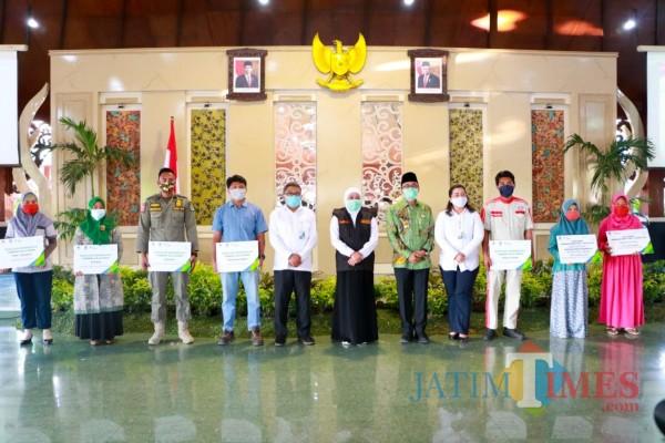 Gubernur Jawa Timur Khofifah Indar Parawansa foto bersama dengan perwakilan penerima bantuan di Pamekasan, (Foto: Rozy/ JatimTimes.com)