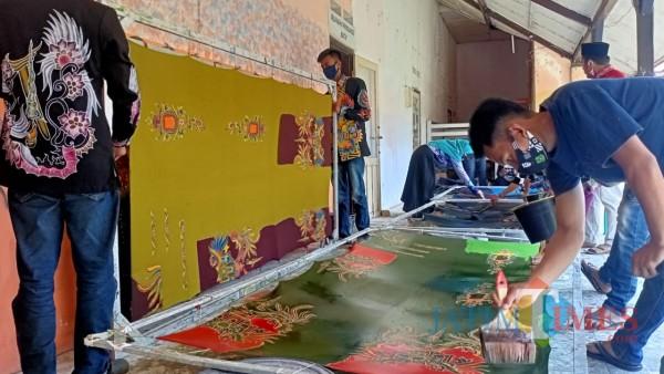 Penuh semangat dan kreatifitas, muda-mudi di rumah produksi Batik Rato WMS tampak serius mengerjakan pewarnaan batik (Foto: Syaiful Ramadhani/JatimTIMES)
