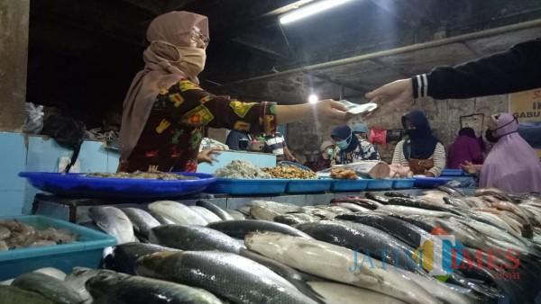 Pedagang saat melayani pembeli ikan di Pasar Besar Malang. (Ahmad Amin/MalangTIMES).