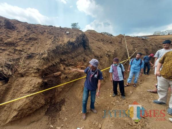 Arkeolog Dwi Cahyono saat mengamati temuan batu bata di lokasi Dusun Ngenep. (Foto: Ody/MalangTIMES).