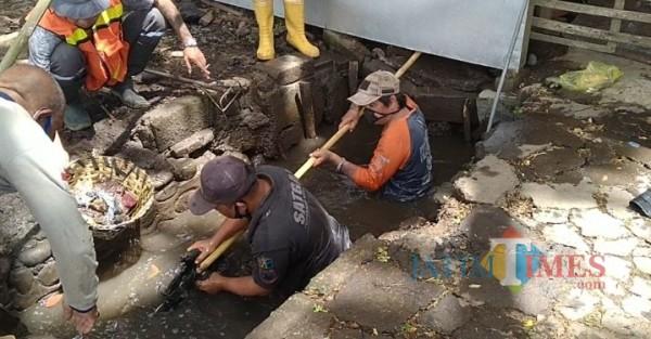 Personel Satgas DPUPRPKP saat melakukan normalisasi saluran drainase di Jalan Raya Arjowinangun (Anggara Sudiongko/ MalangTIMES)