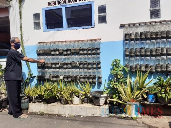 Warga di Kampung DX Patmanam saat merawat tanaman hijau di area depan rumahnya. (Arifina Cahyanti Firdausi/MalangTIMES).