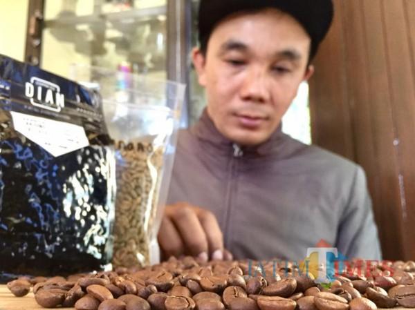 Paimo saat memilah kopi di rumahnya DesaBulukerto, Kecamatan Bumiaji. (Foto: Irsya Richa/MalangTIMES)