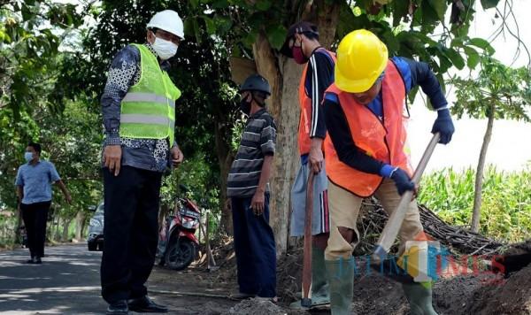 Para pekerja proyek padat karya mengerjakan pembangunan jalan.(ist)