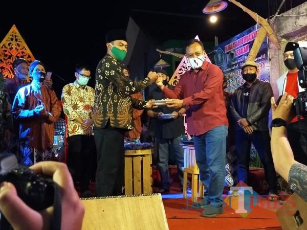 Kepala Dinas Pariwisata Kota Batu Arief As Siddiq memberikan potongan tumpeng kepada kepala Desa Beji Deny Cahyono. (Foto: Muklas/JatimTIMES)
