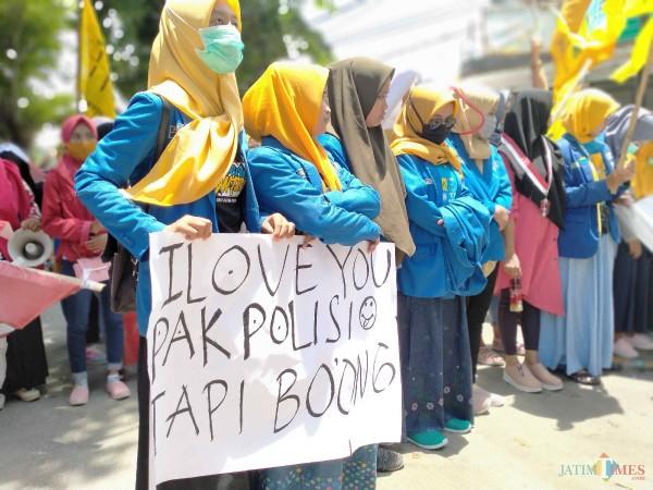 Aktivis perempuan dari Kopri PMII dan GMNI Sumenep membentangkan poster 'I LOVE Pak Polisi Tapi Bohong' saat demo di Mapolres (Foto: Syaiful Ramadhani/ JatimTIMES)