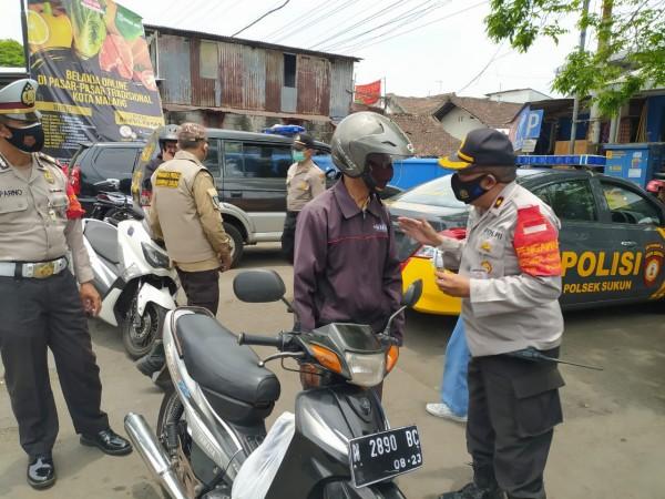 Kapolsek Sukun Kompol Suyoto saat memberikan reward terhadap masyarakat yang patuh pada protokol kesehatan (Ist)