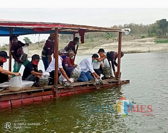 Pasangan calon bupati dan wakil bupati Ngawi Ony Anwar dan Dwi Riyanto Jatmiko  menebar ribuan benih ikan di perairan Waduk Pondok.