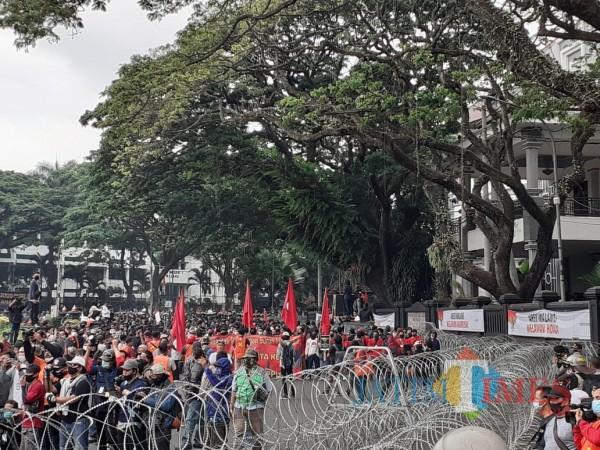 Massa aksi unjuk rasa tolak Omnibus Law UU Cipta Kerja mengepung kawasan depan Gedung DPRD Kota Malang, Selasa sore (20/10). (Arifina Cahyanti Firdausi/MalangTIMES).