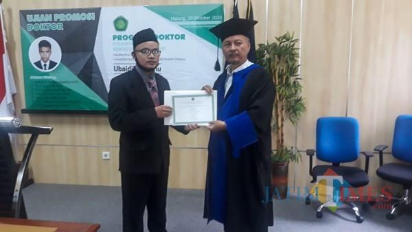 (dari kiri) Doktor baru di UIN Malang Ubaidillah Canu dan Rektor UIN Malang Prof Dr Abdul Haris MAg foto bersama usai ujian promosi. (Foto: istimewa)