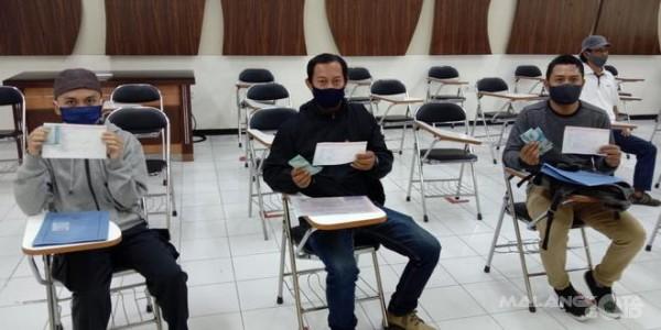 Pegawai yang terkena PHK lantaran pandemi covid-19 saat menerima bantuan tunai dari Disnaker-PMPTSP Kota Malang. (Disnaker-PMPTSP Kota Malang for MalangTIMES).