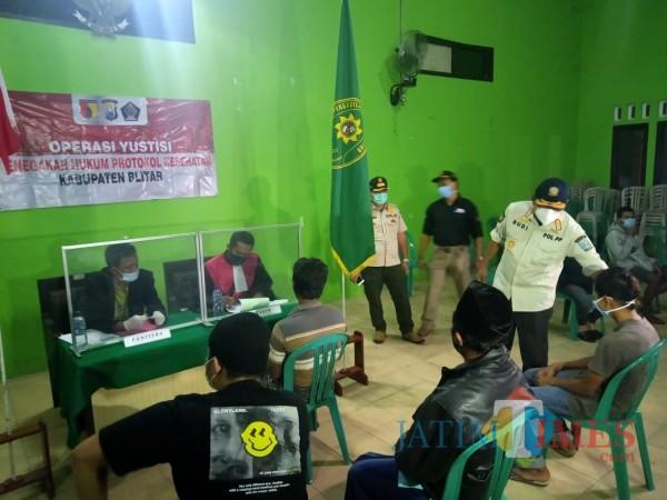 Pjs Bupati Blitar Budi Santosa (baju putih) memberikan sosialisasi 3M kepada warga yang melanggar prokes.(Foto : Aunur Rofiq/BlitarTIMES)
