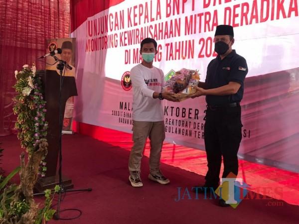 Kepala BNPT RI, Boy Rafli Amar (baju hitam) saat menerima bingkisan makanan ringan produksi dari Syahrul Munif (baju putih), Senin (26/10/2020). (Foto: Dok. JatimTimes)