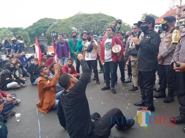 Wali Kota Malang Sutiaji (berbaju hitam bertopi) saat menemui aksi demonstran tolak Omnibus Law UU Cipta Kerja  di depan Balai Kota Malang, Senin (26/10). (Arifina Cahyanti Firdausi/MalangTIMES).