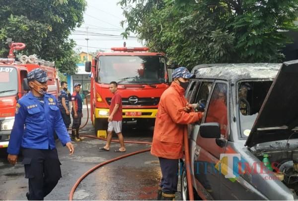 Petugas pemadam kebakaran saat berupaya memadamkan api yang bersumber dari dalam mobil (Foto: PPK Kabupaten Malang for MalangTIMES)