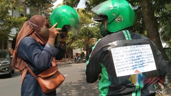 Fachruroziy saat mendapat order, terlihat jaket yang beri pengumuman tarif sukarela (Joko Pramono for Jatim TIMES)