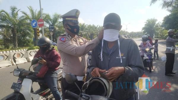 Kasat Lantas Polres Kediri AKP Bobby Mochamad Zulfikar ketika mengenakan masker kepada pengguna jalan. (Foto: Bams Setioko/JatimTIMES)