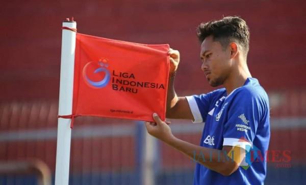 Salah satu pemain Persik Kediri saat memegang bendera LIB.(ist)