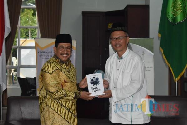 (dari kiri) Wamenag RI Drs H Zainut Tauhid Sa'adi MSi saat menerima buku puisi dari Rektor UIN Malang Prof Dr H Abdul Haris MAg. (Foto: Humas UIN Malang)