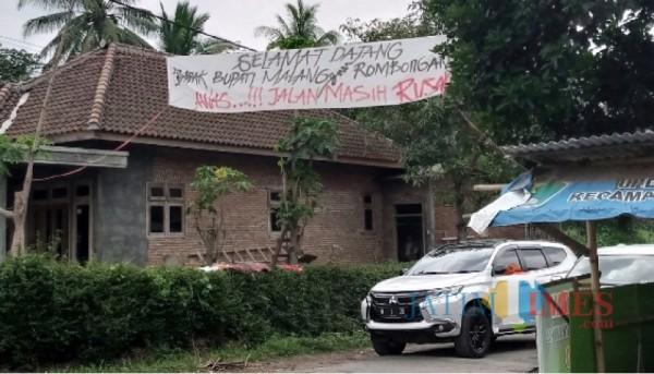 Salah satu spanduk yang bertuliskan aspirasi masyarakat perihal keluhan akses jalan desa yang rusak. (Foto : Istimewa)
