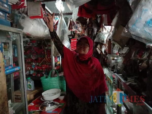 Umi Kalsum, pemilik bengkel saat mengecek barang di bengkelnya. (Anggara Sudiongko/MalangTIMES)