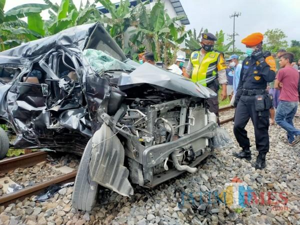 Polisi mengevakuasi bangkai mobil yang terlibat kecelakaan dengan KA di Blitar.