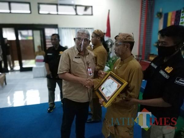 Kepala Dinsos Jatim, Dr Alwi saat memberikan sertifikat kepada klien (Hendra Saputra)