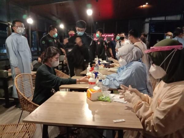 Pengunjung cafe yang terjaring operasi yustisi tengah dirapid test (Ist)