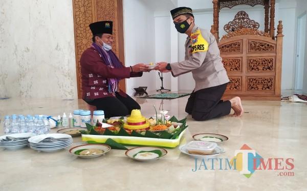 Ustazd H. Soim Alkasi memberikan potongan tumpeng ke AKBP Handono Subiakto / Foto : Anang Basso / Tulungagung TIMES