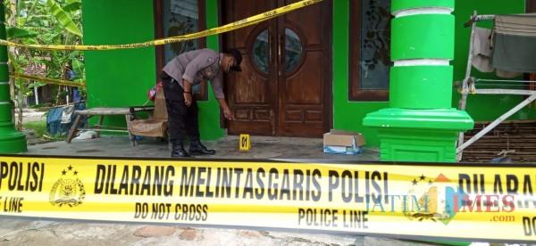 Petugas saat berada di depan rumah korban yang masih dipasangi police line. (Joko Pramono for Jatim TIMES)