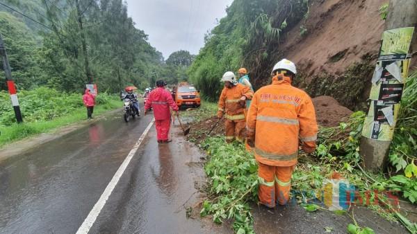 Petugas saat melakukan pembersihan tanah longsor di Jalan Raya Sumber Brantas, DesaSumber Brantas Kecamatan Bumiaji, Minggu (29/11/2020). (Foto: istimewa)