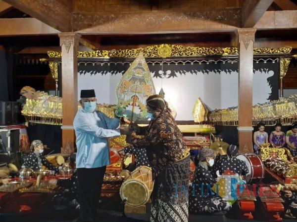 Momen saat Pjs Bupati Malang, Sjaichul Ghulam menerima wayang gunungan dari dalang Ki Setiyo Wahyudi di Museum Singhasari, Sabtu (28/11/2020) malam. (Foto: Dok. JatimTimes)