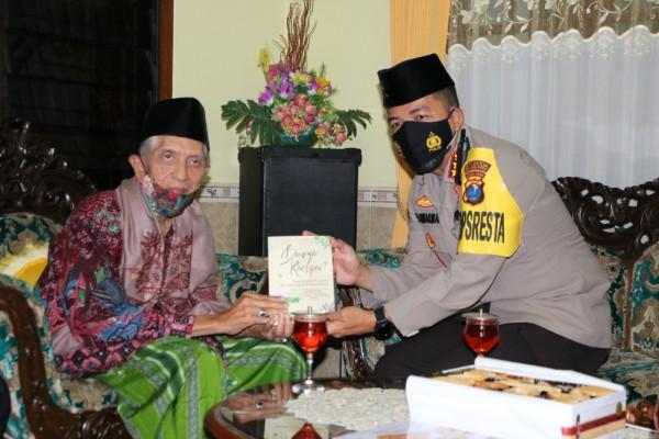Kapolresta Malang Kota Kombespol Leonardus Simarmata saat menerima buku pemberian dari Ketua MUI Kota Malang, KH Baidhowi Muslih (Ist)